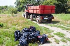 Trator que recolhe sacos de lixo Fotografia de Stock Royalty Free