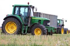 Trator que trabalha em um campo durante a colheita Fotografia de Stock