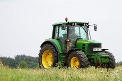 Trator que trabalha em um campo durante a colheita Foto de Stock