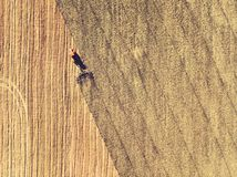 Trator que trabalha nos campos, vista aérea, feno no campo A vista da parte superior O trator colhe a grama seca fotos de stock