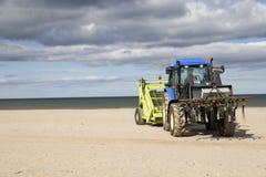 Trator rodado para a areia da limpeza na praia Fotografia de Stock