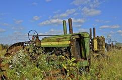Trator verde velho enterrado nas ervas daninhas Foto de Stock Royalty Free