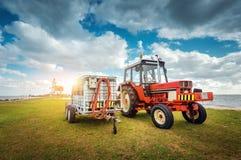 Trator vermelho com o reboque no campo de grama Imagem de Stock