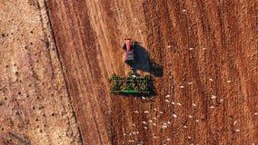Trator vermelho da cabine que ara o campo com guilhotina verde, vista aérea filme
