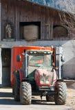 Trator vermelho e estátua religiosa em uma exploração agrícola imagens de stock royalty free