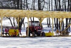 Trator vermelho estacionado sob um telhado de madeira Foto de Stock Royalty Free