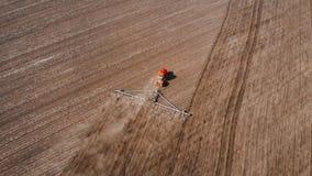 trator vermelho moderno da metragem 4K aérea no campo agrícola no dia ensolarado Trator que ara a terra Cultura do trator filme