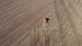 trator vermelho moderno da metragem 4K a?rea no campo agr?cola no dia ensolarado Trator que ara a terra Cultura do trator filme