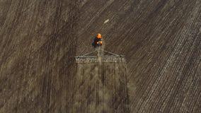 trator vermelho moderno da metragem 4K a?rea no campo agr?cola no dia ensolarado Trator que ara a terra Cultura do trator video estoque
