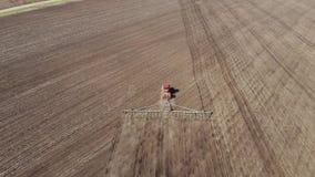 trator vermelho moderno da metragem 4K a?rea no campo agr?cola no dia ensolarado Trator que ara a terra Cultura do trator vídeos de arquivo