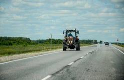 Trator vermelho na estrada Imagem de Stock