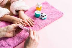 Trattamenti della stazione termale per la pelle ed i chiodi della mano per i bambini La mamma fa un manicure della ragazza a casa immagine stock libera da diritti