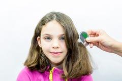 Trattamento dei pidocchi La ragazza ottiene pettinata per i pidocchi con il pettine dei pidocchi Ritratto dello studio Fotografie Stock