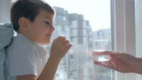 Trattamento del bambino che prende la pillola e beve giù l'acqua minerale da vetro trasparente nella sala archivi video