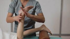 Trattamento della medicina alternativa Fisioterapista che esercita la gamba di una bambina in un ufficio di fisioterapia con il m archivi video