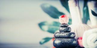 Trattamento della stazione termale con la pila di pietre di massaggio, di fiori e di asciugamani neri, concetto di benessere Immagine Stock Libera da Diritti
