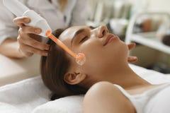 Trattamento di bellezza del fronte Donna che per mezzo del dispositivo di cura di pelle di Darsonval Fotografia Stock Libera da Diritti