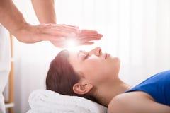Trattamento di Performing Reiki Healing del terapista sulla donna fotografie stock