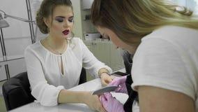 Trattamento, macinazione e lucidatura dell'unghia del dito nel salone di bellezza Manicure il processo nel salone di bellezza, fi video d archivio