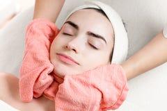 Trattamento o massaggio facciale della giovane donna con l'asciugamano Fotografie Stock