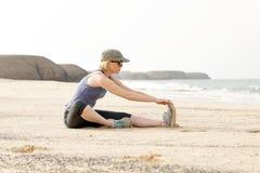 Tratto attivo di signora Doing Seated Hamstring dalla spiaggia Immagine Stock Libera da Diritti
