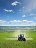 Trattore agricolo che ara e che spruzza sul campo Immagini Stock Libere da Diritti