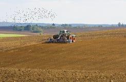 Trattore agricolo che coltiva sul terreno coltivabile Fotografia Stock Libera da Diritti