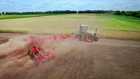 Trattore agricolo con il rimorchio per l'aratura lavorare al campo coltivato stock footage