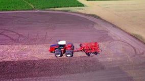 Trattore agricolo con il rimorchio per lavorare d'aratura al campo coltivato stock footage
