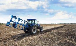 Trattore agricolo con l'aratro Immagini Stock