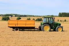 Trattore agricolo di John Deere 5820 con il rimorchio pieno di grano Fotografia Stock