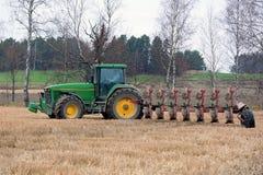 Trattore agricolo di John Deere 8100 ed aratro di Kverneland PB100 Fotografia Stock