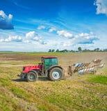 Trattore agricolo di vista con l'aratro che sta sul campo Fotografie Stock Libere da Diritti