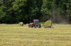Trattore agricolo su Hayfield Fotografia Stock