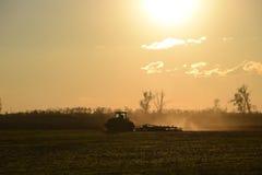 Trattore all'aratro dell'aratro di tramonto un campo Lavorando il suolo nella caduta dopo il raccolto la conclusione della stagio Immagini Stock Libere da Diritti