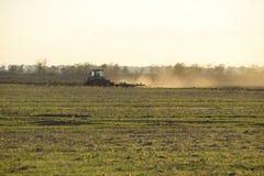 Trattore all'aratro dell'aratro di tramonto un campo Lavorando il suolo nella caduta dopo il raccolto la conclusione della stagio Fotografie Stock