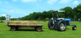 Trattore blu d'annata con il vagone del fieno nel sud-ovest Wisconsin immagini stock