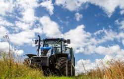 Trattore blu moderno che tira un rimorchio nel campo del raccolto Immagine Stock