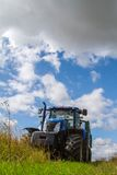 Trattore blu moderno che tira un rimorchio nel campo del raccolto Fotografia Stock