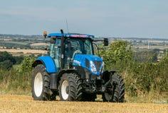 Trattore blu moderno che tira un rimorchio nel campo del raccolto Immagini Stock