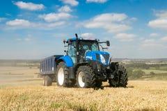 Trattore blu moderno che tira un rimorchio nel campo del raccolto Immagini Stock Libere da Diritti