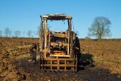 Trattore bruciato scavatore nel campo arato Fotografia Stock