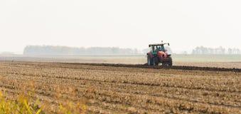 Trattore che ara i campi - preparare terra per la semina in autunno Fotografie Stock Libere da Diritti