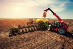 Trattore che ara il campo dell'azienda agricola in preparazione della piantatura della molla Immagini Stock