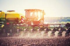 Trattore che ara il campo dell'azienda agricola in preparazione della piantatura della molla Immagine Stock Libera da Diritti