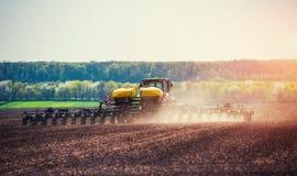 Trattore che ara il campo dell'azienda agricola in preparazione della piantatura della molla Fotografie Stock Libere da Diritti