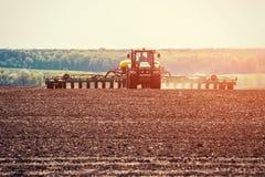 Trattore che ara il campo dell'azienda agricola in preparazione della piantatura della molla Fotografia Stock Libera da Diritti