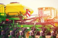 Trattore che ara il campo dell'azienda agricola in preparazione della piantatura della molla Fotografia Stock