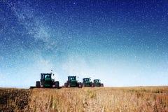 Trattore che ara il campo dell'azienda agricola in preparazione della piantatura della molla Cielo stellato fantastico e la Via L Immagine Stock Libera da Diritti