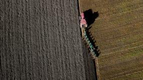 Trattore che ara il campo fotografia aerea da un fuco immagini stock libere da diritti